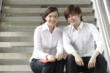 Portrait of Asian Business man and woman sitting on stairs  photo