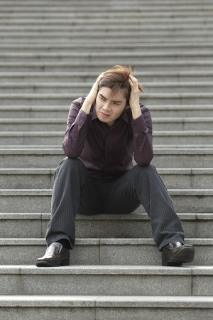 Asian business man sitting steps looking Anxious photo