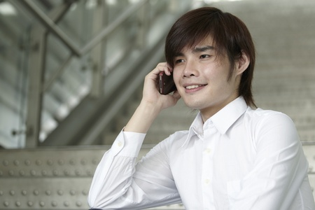 Asian Business man using a mobile Phone while sitting on stairs photo