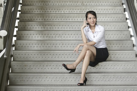 Business woman using a mobile phone on the stairs photo
