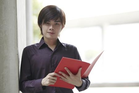 Portrait of an Asian Business man holding a folder photo