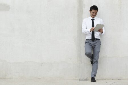 Asian Business man using a touch pad PC Stock Photo - 10670232