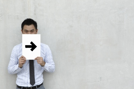 A conceptual image about direction. The Asian Business man is holding an arrow sign. photo