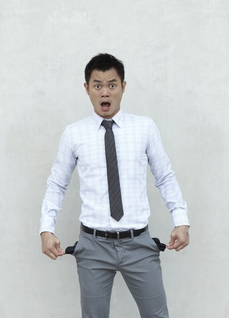 Conceptual image. Asian Businessman stands holding his pockets out showing he has no money. photo