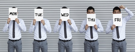 Conceptual image about the working week. Asian business man holding signs with the days of the week writen on them. photo