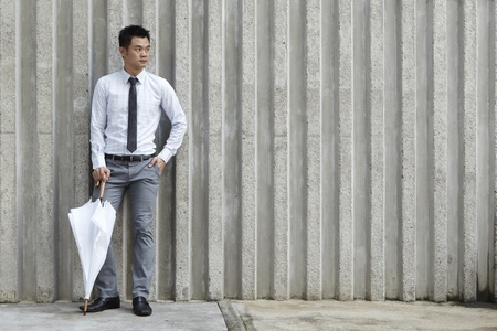 south asian ethnicity: Asian business man leaning on a wall waiting for something while holding an umberella. Stock Photo