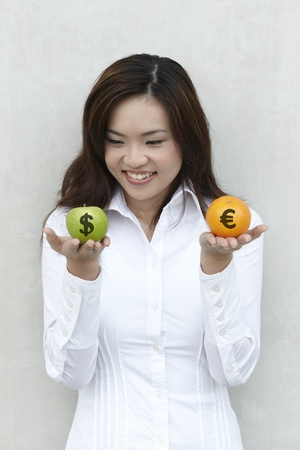 A conceptual image about choice. The Asian woman holding an apple and orange with US $ and Euro symbols drawn on them.  photo