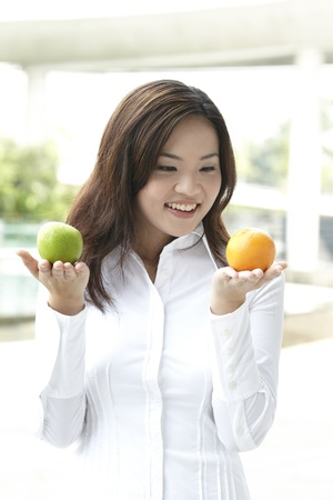 south east asian: A conceptual image about choice. The Asian woman holding an apple and orange.