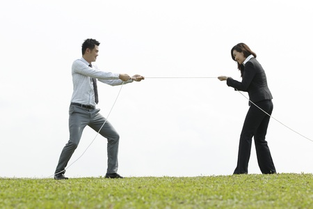Asian Business people playing tug of war. A Conceptual image. photo