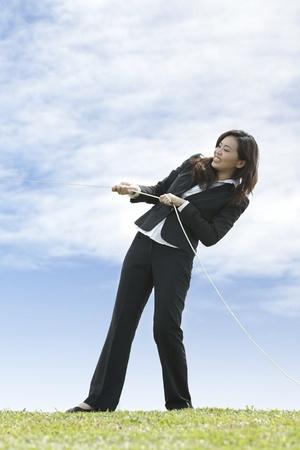 Conceptual image, Asian Business woman playing tug of war photo