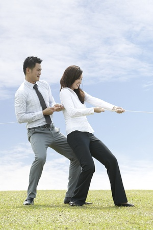 Conceptual image. Asian Business people playing tug of war photo