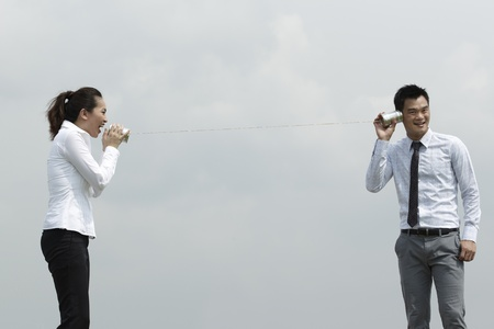 This conceptual image is about communication. Asian Business man and woman using Tin Can Phone. photo
