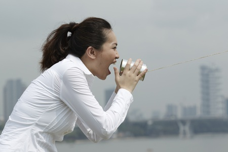 This conceptual image is about communication. Asian Business woman shouting into a Tin Can Phone. photo