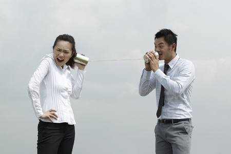 This conceptual image is about communication. Asian Business man and woman using Tin Can Phone. Stock Photo