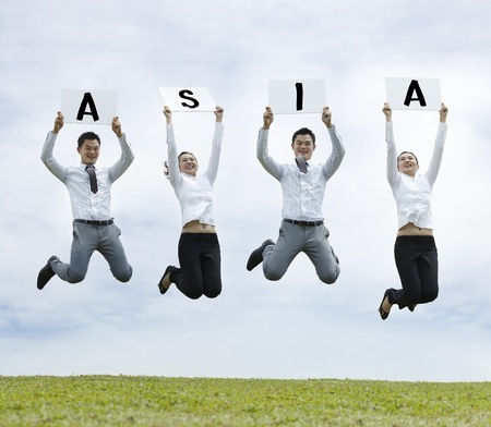 winning business woman: Conceptual Stock image of an Asian man & woman jumping holding sign  Stock Photo