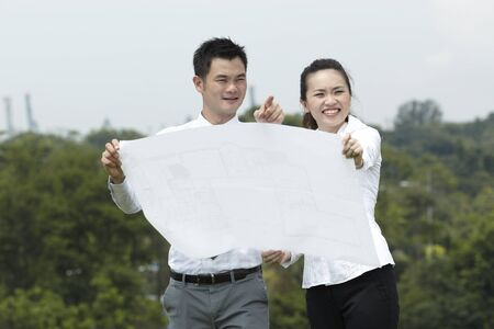 Asian couple standing outside looking at blueprints. Stock Photo - 10963427