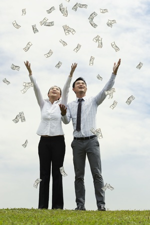 Conceptual Stock image of a man & woman standing with open arms amidst falling money photo