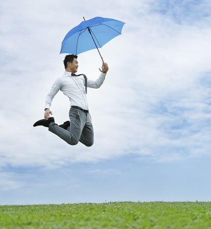 Conceptual Stock image of an Asian business man jumping for joy photo