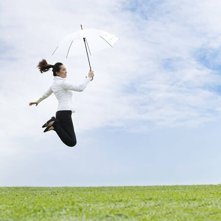 Conceptual Stock image of an Asian business woman jumping for joy photo