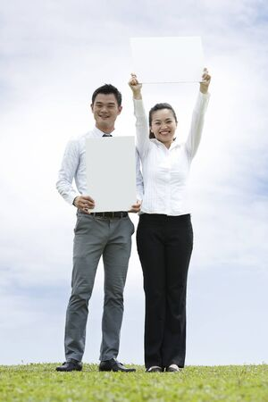 south asian ethnicity: Conceptual Stock image of an Asian business man & woman holding sign  Stock Photo