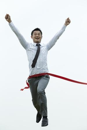 Conceptual image of an Asian Business man winning a race photo
