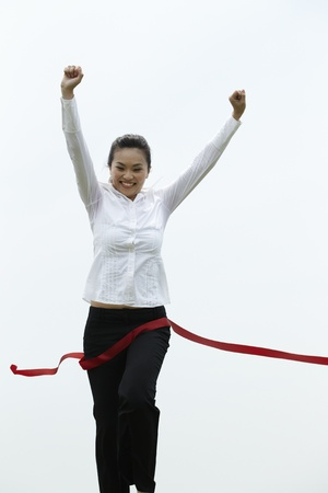 Conceptual image of an Asian Business woman winning a race photo