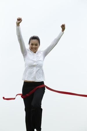 Conceptual image of an Asian Business woman winning a race photo
