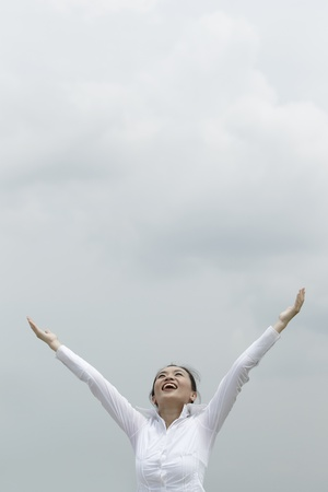 asian travel: Conceptual stock image of an Asian woman with arms raised
