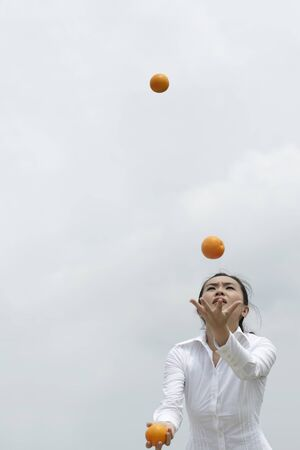 south asian ethnicity: Conceptual image of an Asian Business woman juggling oranges