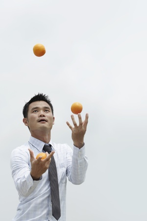 talents: Conceptual image of an Asian Business man juggling oranges