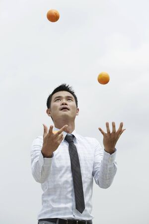 south asian ethnicity: Conceptual image of an Asian Business man juggling oranges