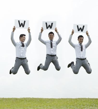businessman jumping: Conceptual Stock image of an Asian man & woman jumping holding sign  Stock Photo