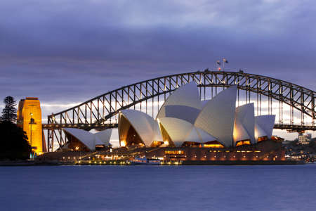 Sydney, Australia - July, 20th 2010; The iconic Sydney Opera House viewed with the Sydney Harbor Bridge in the background at dusk  View looking west across Sydney Harbor