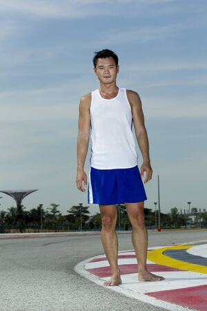 Asian man standing outside ready to exercise photo