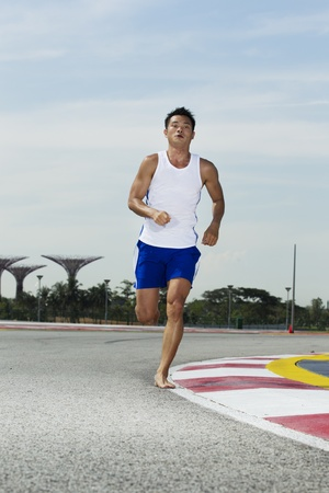 Asian male running barefoot on a track Stock Photo