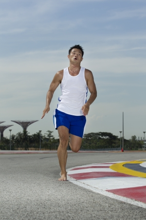 bare foot: Asian male running barefoot on a track Stock Photo