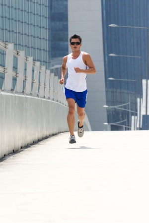 Asian male jogging in day with skyscraper behind photo