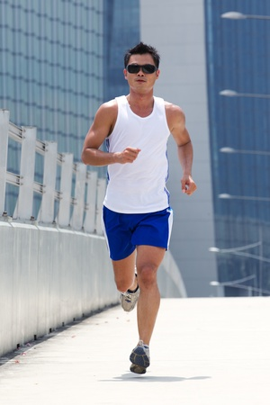 Asian male jogging with skyscraper in background photo