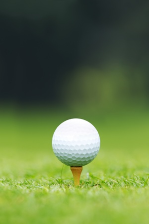 A close-up of a Golf ball sitting on a tee