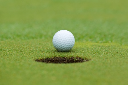 A golf ball sitting behind a hole photo
