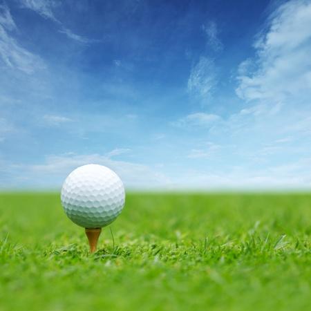 Golfbal op tee met blauwe hemel achter