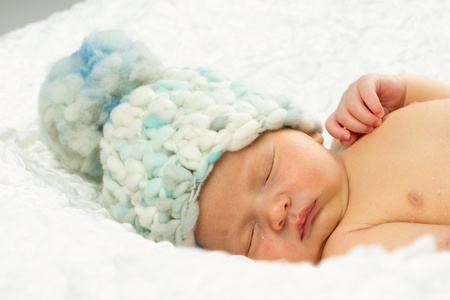 Newborn Baby boy sleeping while wearing a hat on his head. photo