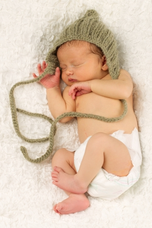 Newborn Baby boy sleeping while wearing a hat on his head. photo