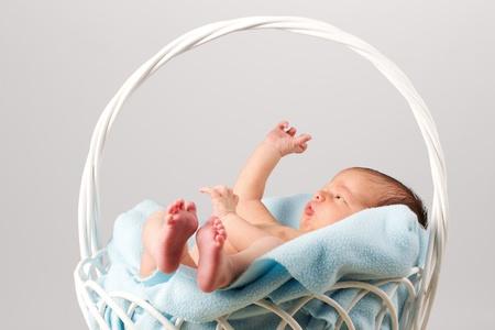 bebe sentado: Beb� reci�n nacido pac�fico sentado en una cesta de manta-rayas.