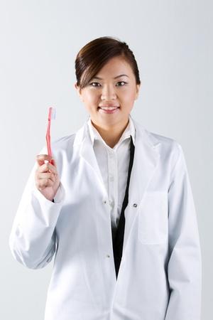 Female Asian Dentist wearing a white coat. photo