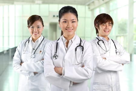 Three Asian doctor wearing a white coats with stethoscopes. photo
