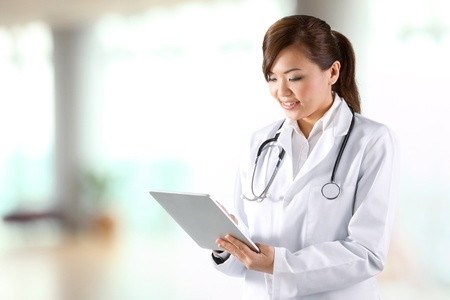アジア女医デジタル タブレットを使用して & 白いコートを着ています。