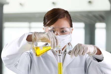 A female scientific researcher looking at a liquid solution. Stock Photo - 12228546
