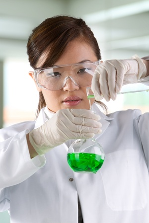 A female scientific researcher looking at a liquid solution. photo