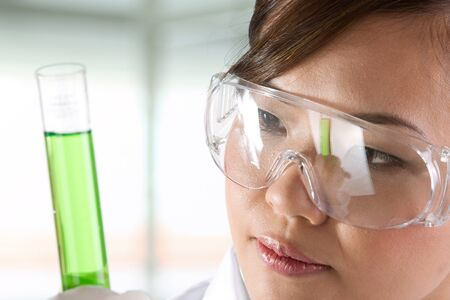 A female scientific researcher looking at a liquid solution. Stock Photo - 12228553